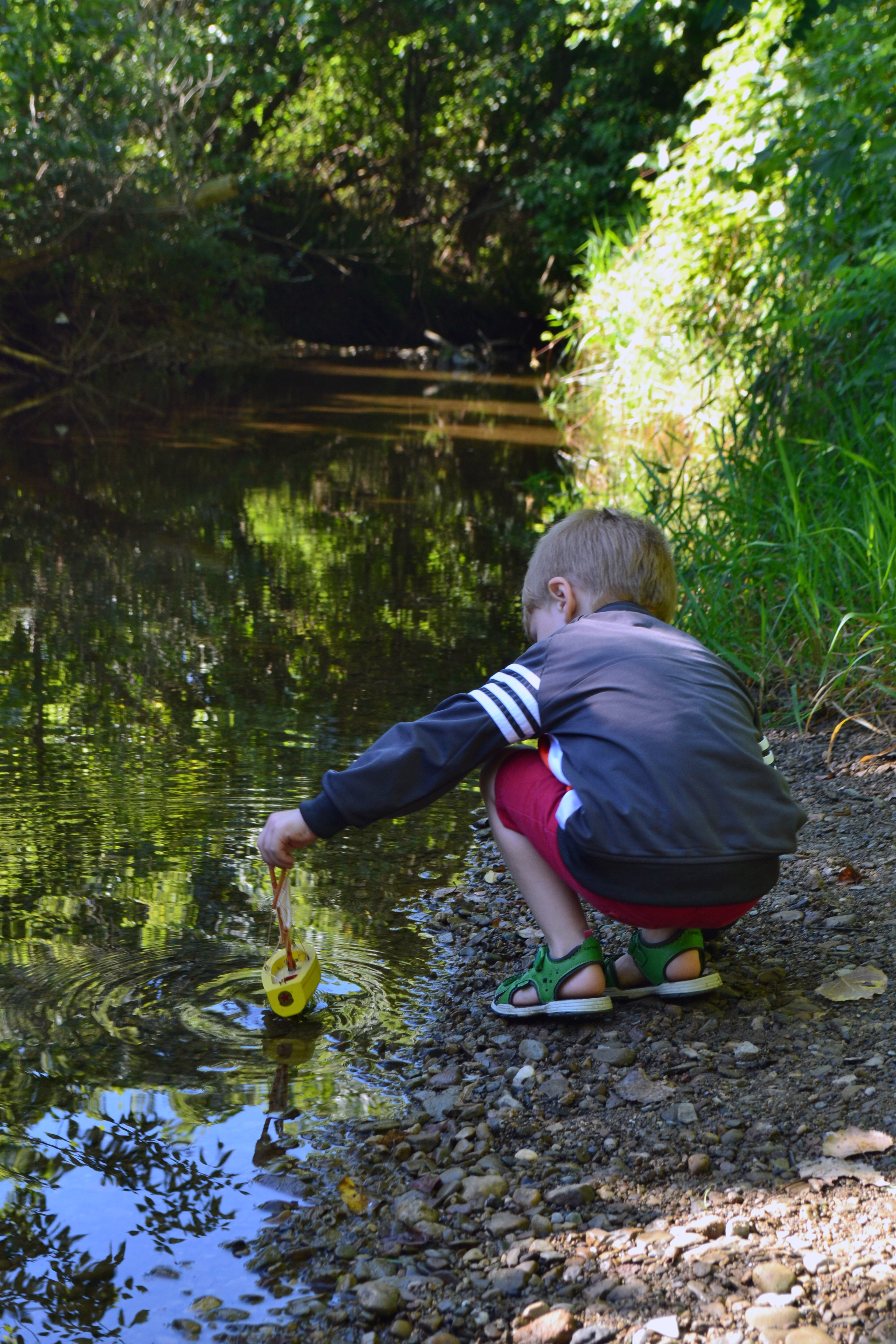 child in stream with toy sailboat