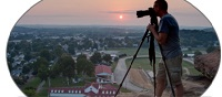 Man looking through a camera on a tripod over the city