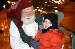 A little boy with a red coat and black hat sitting on Santa's lap