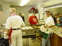 A group of men in the kitchen cooking pancakes and serving a crowd