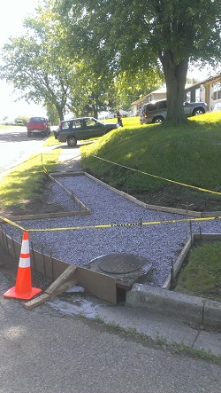 Sidewalk and curb ramp under construction with an orange traffic cone and yellow tape