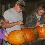 2 adults and a child carving pumpkins for the Pumpkin Hike